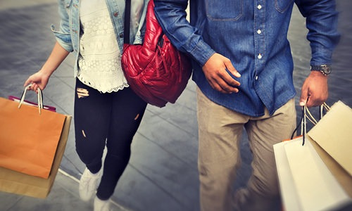 man and woman walking down sidewalk with shopping bags